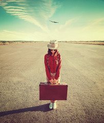 Traveler girl with suitcase standing on runway
