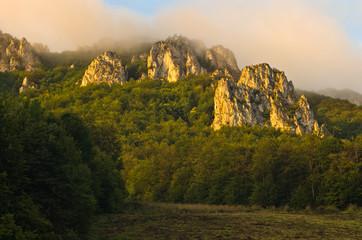 Rocky peaks at foggy sunrise, trekking at Suva Planina mountain