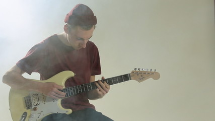Guy in hat playing guitar in the studio in smoke