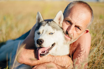 Old man plays with his dog Siberian Husky. Lifestyle.