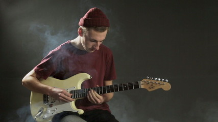 Thoughtful guitarist playing guitar in dark studio