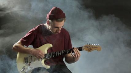 Young guy playing guitar in a dark studio in smoke