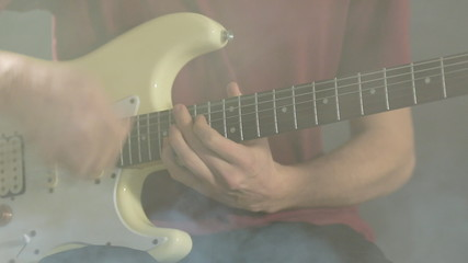 Close-up of a young man playing guitar in a dark studio in smoke