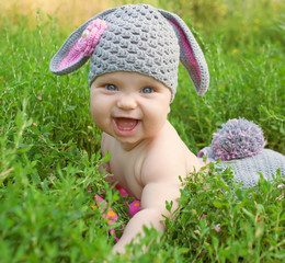 Happy baby easter bunny in green grass.