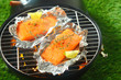 Salmon fillets grilling on an open fire - 79943084