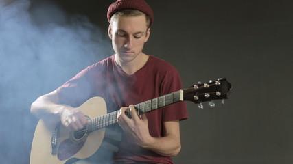 Talented young musician playing guitar in a dark studio in smoke