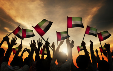 Group of People Waving Flag of UAE in Back Lit Concept