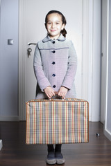 Niña con abrigo y maleta sonriendo