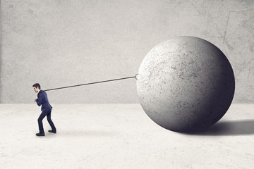 worker guy pulling big rock ball