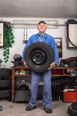 Happy senior worker changing tire in garage