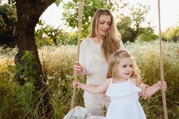 Мама катает дочку на качеле