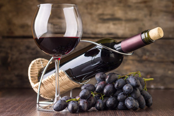 Winery background. Wineglass with bottle of red wine and cluster