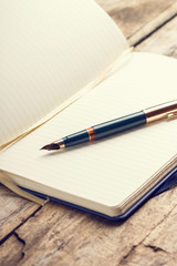 Opened blank notebook with elegant fountain pen