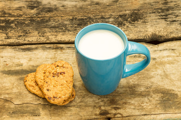 Blue cup of milk with cookies on wooden background