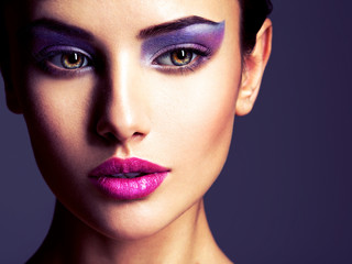 Beautiful girl's face closeup with purple eye make-up. fashion m