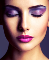 The girl's face closeup with purple eye make-up. fashion makeup