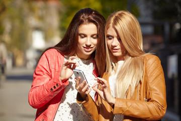 Two beautiful young womenlooking photos on smartfon.
