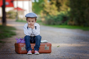 Little boy with suitcase and map, traveling