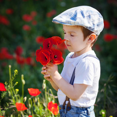 Cute kid boy with poppy flower on poppy field on warm summer day