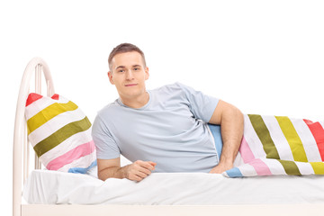Carefree young man lying in a bed