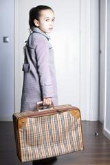 Niña triste con maleta en la puerta de casa