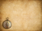 Brass compass on blank vintage paper background