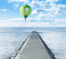 Old pathway into the sea with hot air balloon over