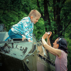 Mom takes pictures of  son on vintage military vehicle.