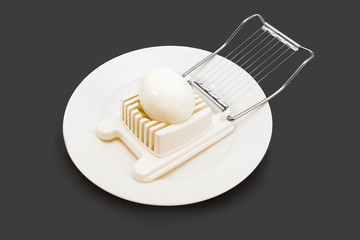 Boiled egg in an egg slicer isolated on black background