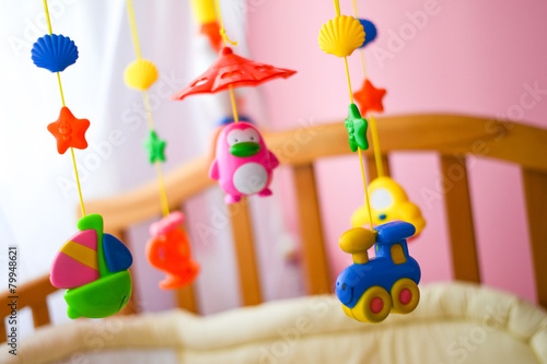 Children toys hanging from the crib - 79948621