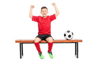 Joyful junior soccer player gesturing happiness