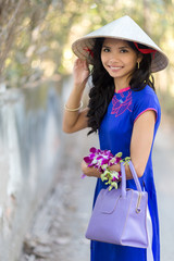 Vietnamese woman in blue Ao Dai holding flowers