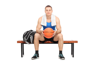 Male basketball player sitting on a bench