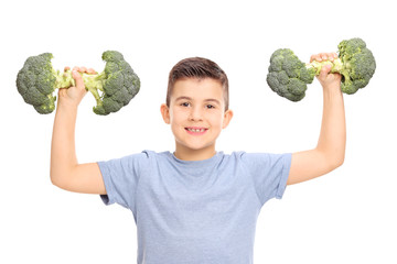 Little kid holding two broccoli dumbbells