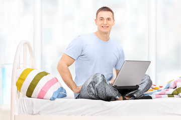 Man in pajamas working on a laptop seated on a bed