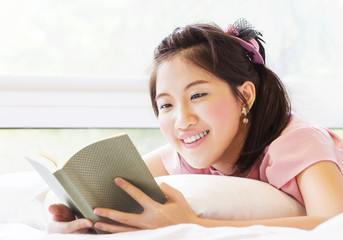 Cute young woman reading book on the bed