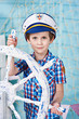 Little boy captain with steering wheel on ship