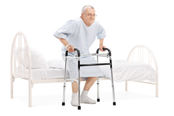 Mature patient getting up from bed with walker