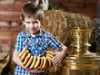 Little boy with bread-rings around large samovar