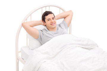 Relaxed young man lying in a comfortable bed