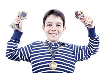 Niño mostrando orgulloso sus trofeos de pádel