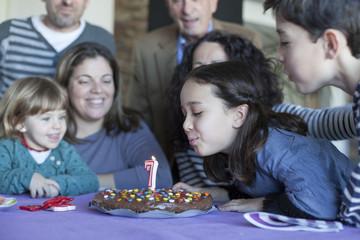 Niña soplando vela de su séptimo cumpleaños