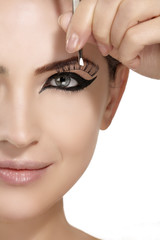 Model applying artificial eyelashes extension on smoky eye