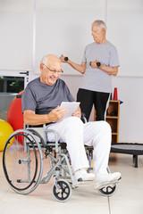 Mann im Rollstuhl mit Tablet Computer