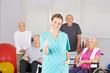 Physiotherapeut vor Gruppe Senioren hält Daumen hoch