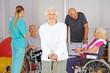 Alte Frau vor Gruppe Senioren im Pflegeheim