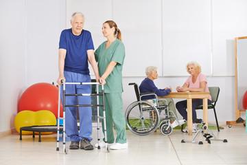 Alter Mann mit Gehgestell bei Physiotherapie