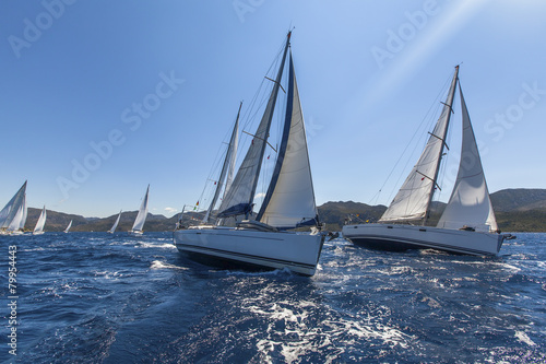 Fotobehang Jacht Sailing ships yachts with white sails in the open sea.