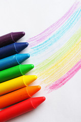 Oil pastel crayons lying on a paper with pictured rainbow