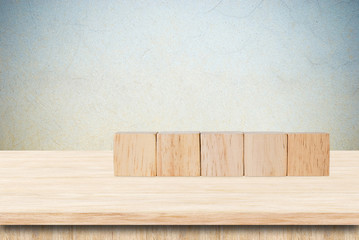 Five wooden cubes on table over grunge cement wall